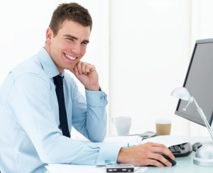 Happy young business man at desk using computer